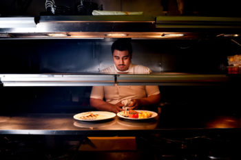 A chef in his kitchen looking at food between heat lamps.