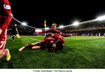 A wide angle photograph of players on top of one another celebrating during a football match between Aberdeen v Rangers. Aberdeen win 1-0.