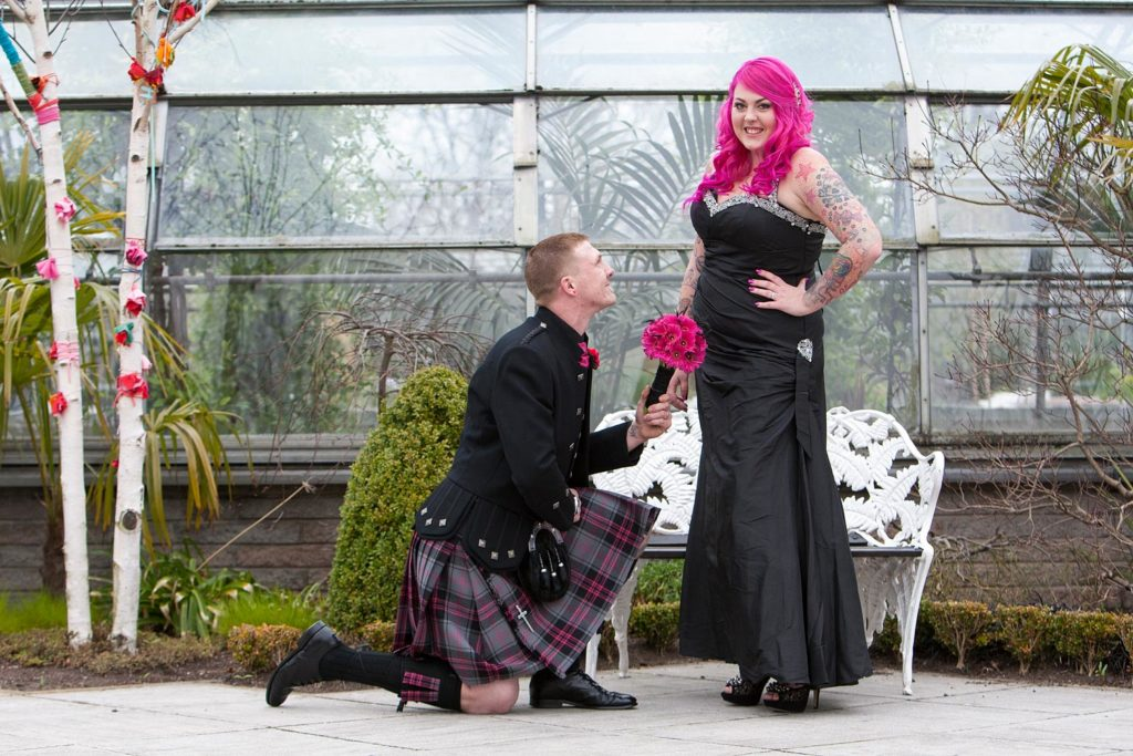 A man in a kilt gets down on one knee to recreate a moment