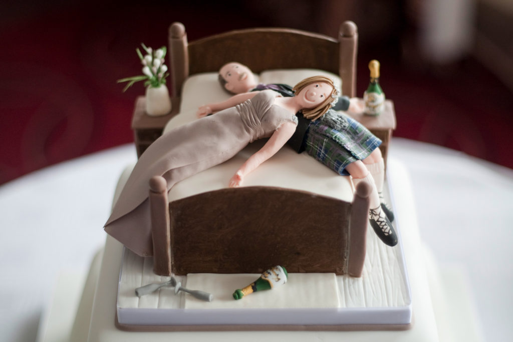 A wedding cake that looks like the couple lying on bed with champagne bottles laying around