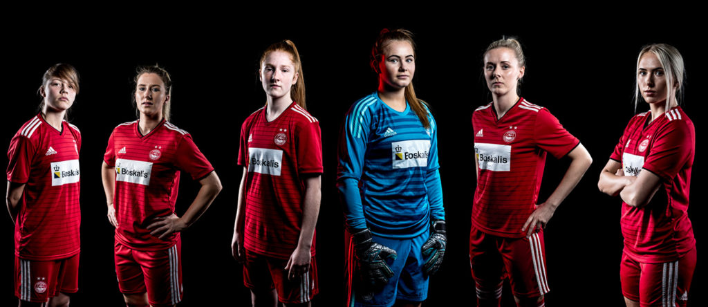 6 women from the Aberdeen FC ladies team pose against a black background.