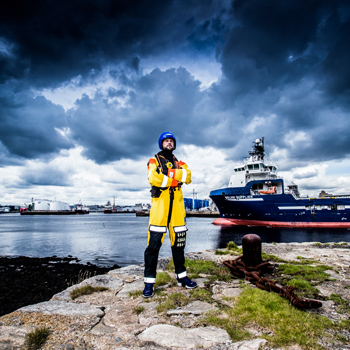 Man in survival suit in front of a boat at the harbour. Link to the commercial portfolio