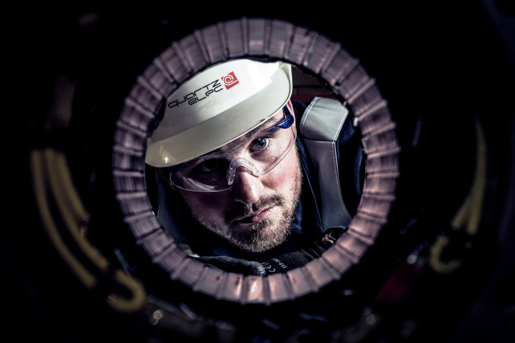 Man in boiler suit and helmet looks through a tubular pipe.