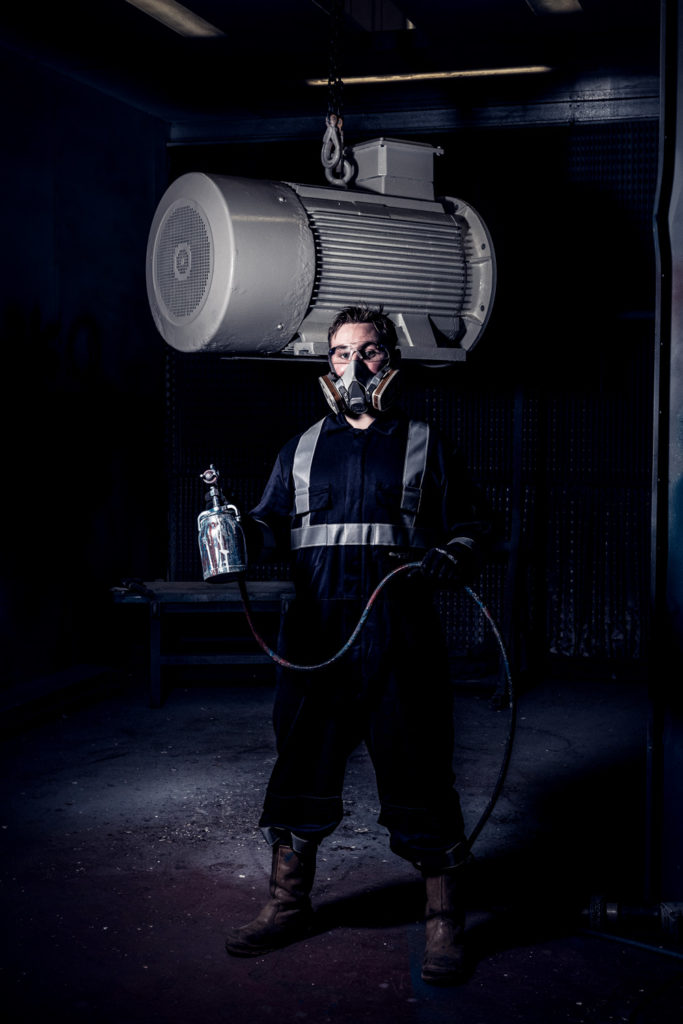 Man in boiler suit and respirator with paint sprayer poses in front of a spray booth.