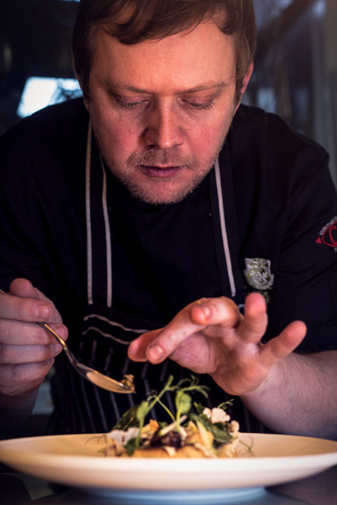 A chef places some garnish onto a dish in this close up photograph