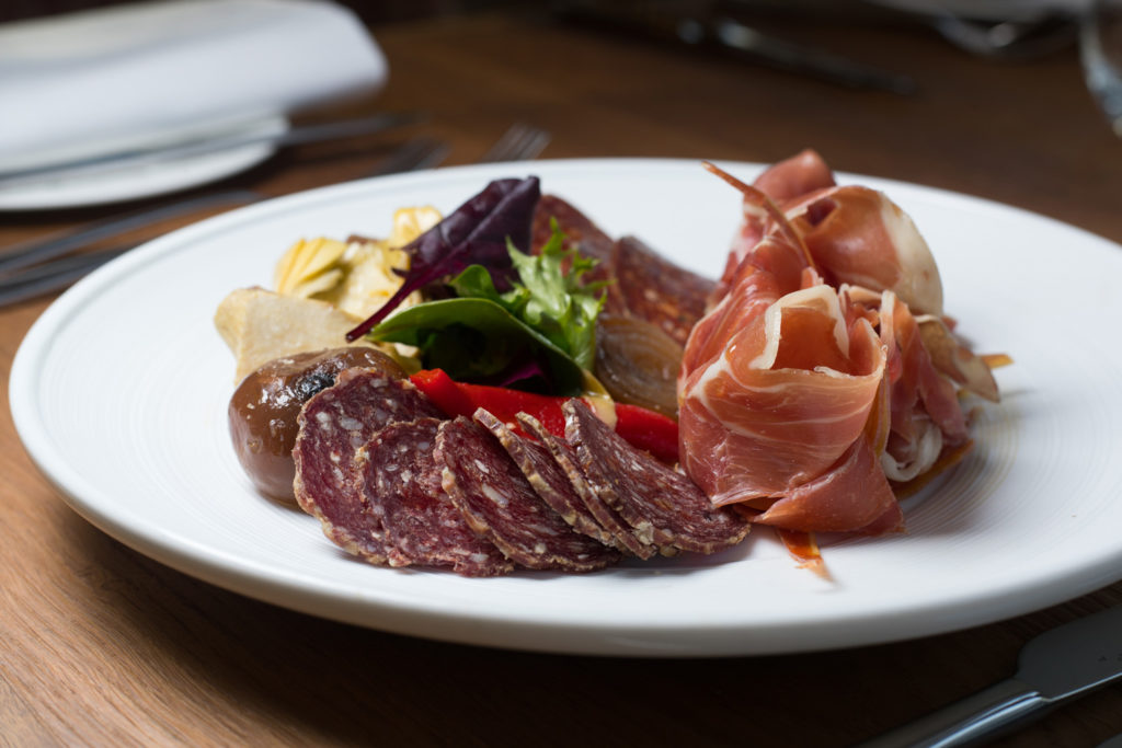 A selection of cured meats on a plate. side on photo.