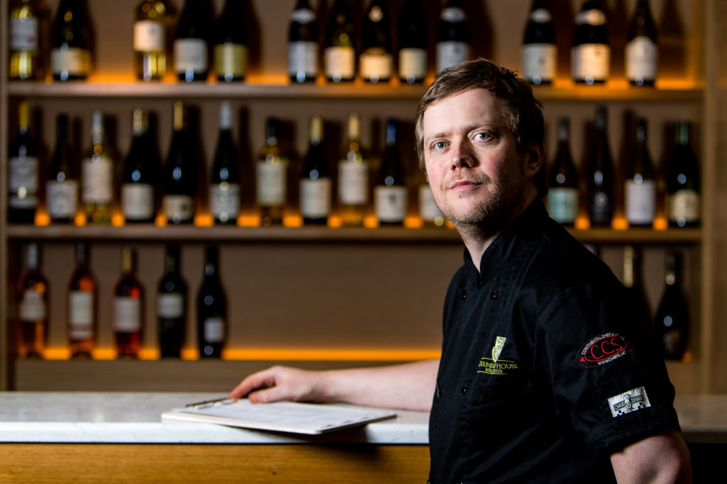Chef Butters from Douneside House Hotel poses for a photograph in front of a wine rack