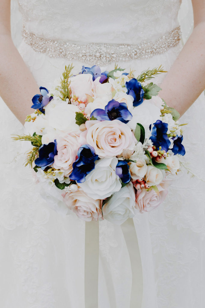 A bunch of flowers against the brides dress.