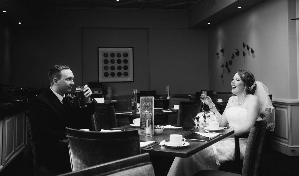 Black and white image of a couple after being married taking a break in a quiet room of a hotel
