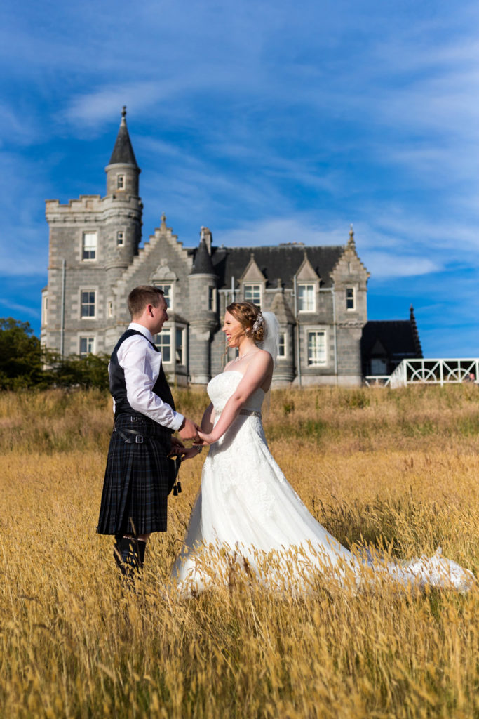 Wedding Photography Aberdeen - A couple pose infant of Ardoe House in a wheat field
