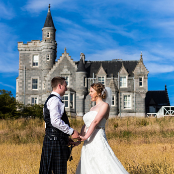 Bride and Groom posing in front of Ardoe house, Aberdeen. Links to the wedding portfolio.