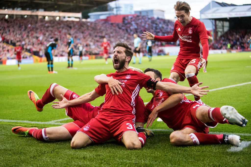 Sports Photography Aberdeen - Four Aberdeen FC players sliding in front of the camera celebrate a late winning goal.