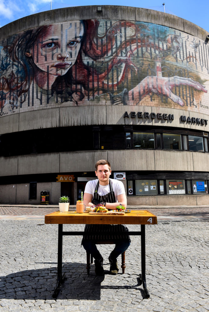 A restaurant owner sits outside his restaurant in the sun with a wooden table and various dishes he has made.