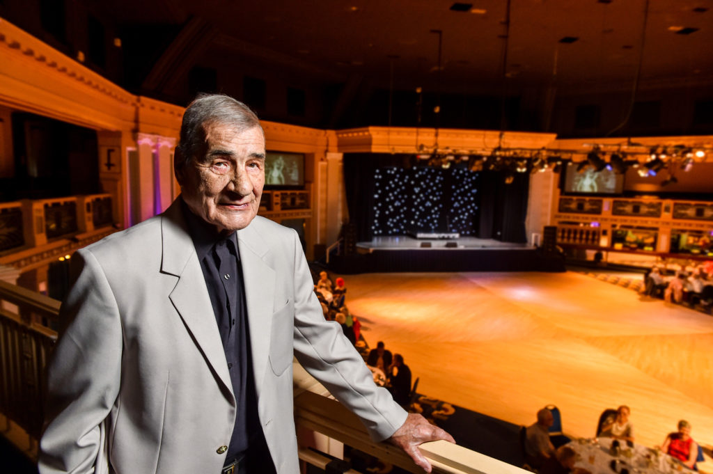 A former ballroom dancer who is 93 years old poses on the balcony of the Aberdeen Beach Ballroom.