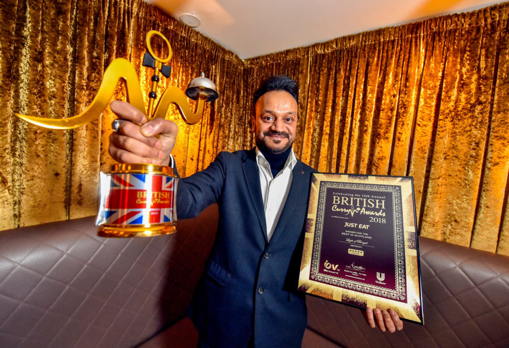 A man holds his trophy and framed certificate for the Best Curry award in Scotland in front of a gold background.