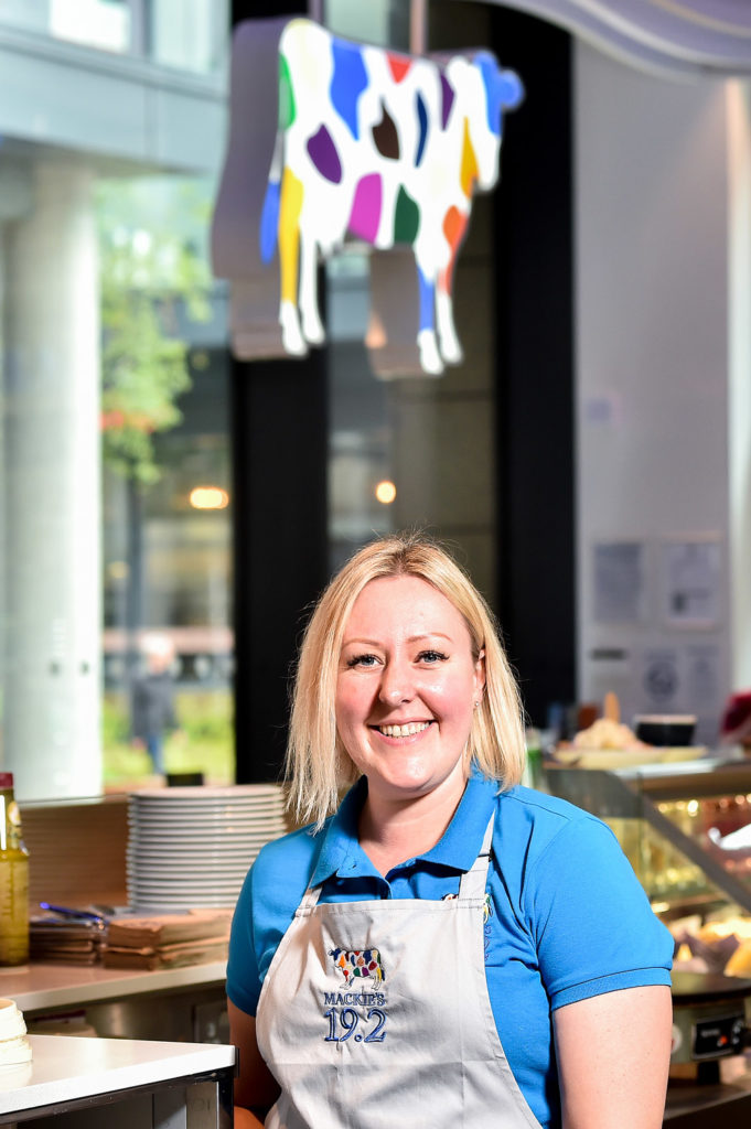 PR Photography: A woman at an ice cream shop poses behind the counter for a portrait style photograph with their logo in the background