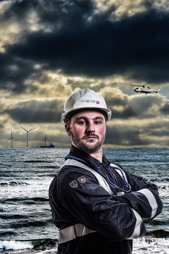 Man in boiler suit with wind farm in background and offshore helicopter.