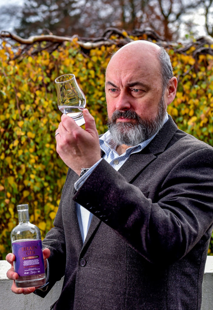 food and drink photography. A Gin distillery owner holds a bottle of Raven Gin in a glencairn glass outside.