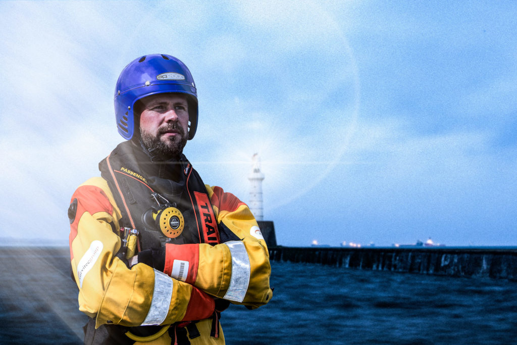 Commercial photography gallery: Man in Offshore Survival suit at Aberdeen breakwater with lighthouse in background
