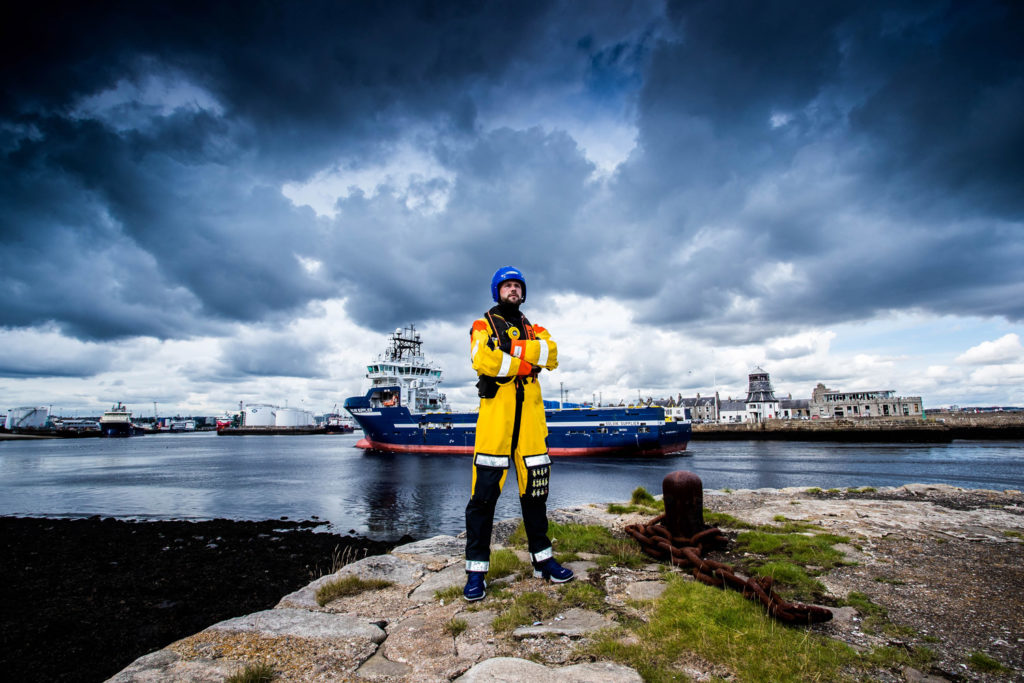 Man in offshore survival suit poses at Aberdeen harbour with vessel entering the harbour in the background