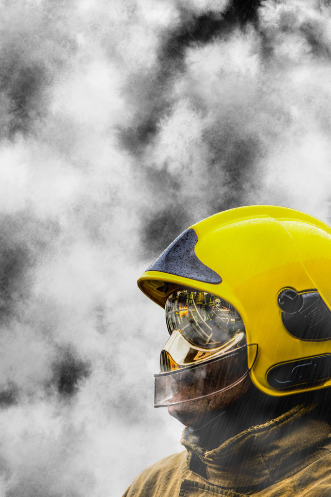 Firefighter in training, a close up photograph of a firefighters helmet with reflective visor with smoke in the background.