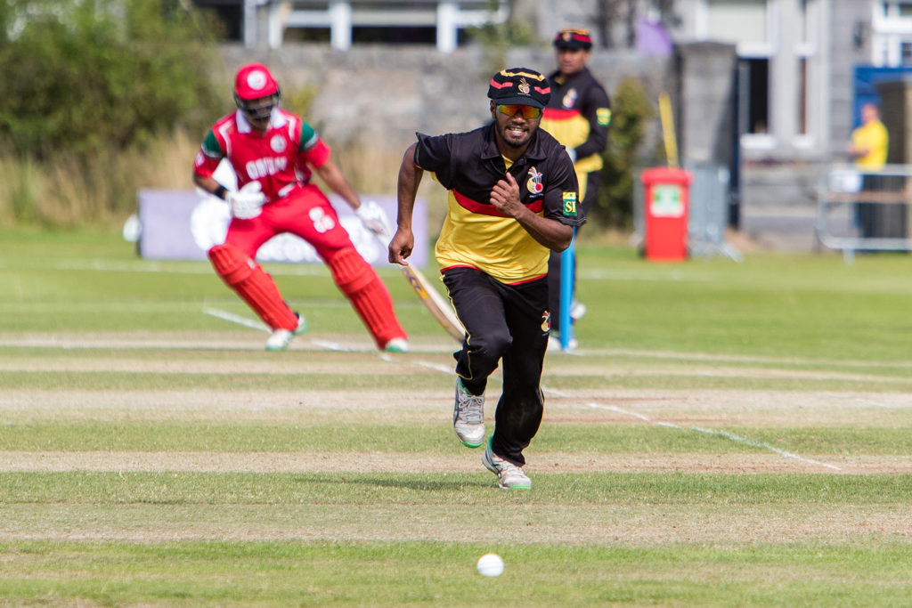 Sports Photography Aberdeen, Pictured is PNG v Oman cricket teams. Image shows PNG cricketer running after the ball with the Oman batsmen making a run in the background in red strip.