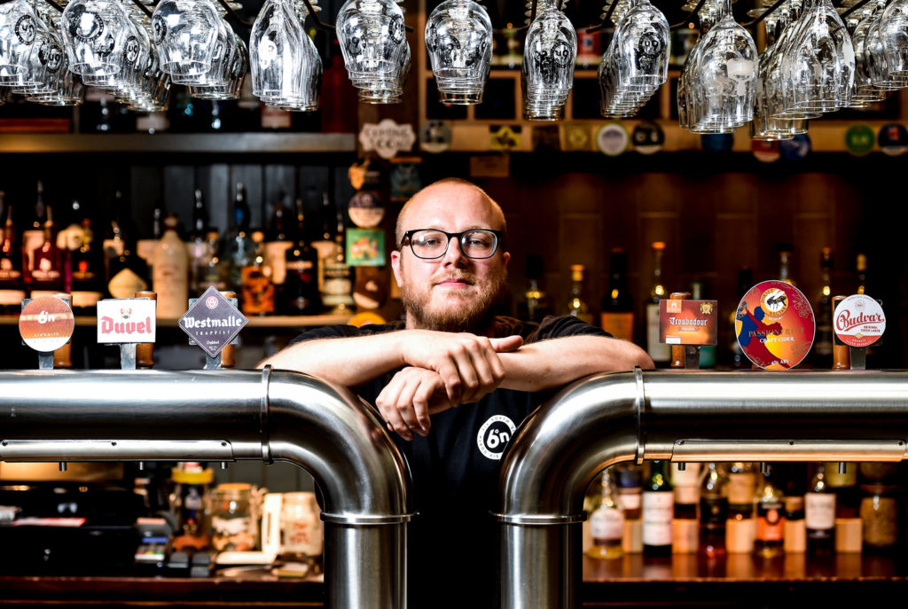 food and drink photography. The bar manager of Six Degrees North poses between the taps on the bar for a photo