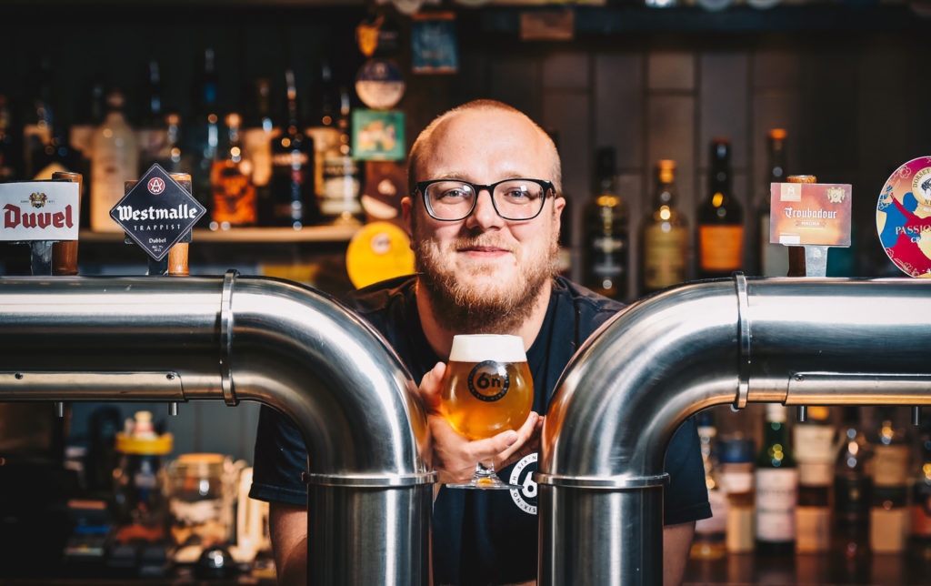 food and drink photography. A cold beer in a glass from 6 Degrees North in Aberdeen held by the bar manager. between two steel beer taps. PR Imagery by Scott Cameron Baxter.