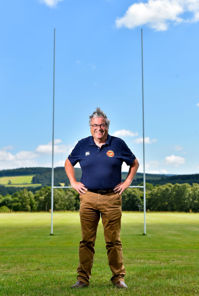 Rugby club chairman of Deeside Rugby Club poses for photos on a very sunny day between the rugby field posts.