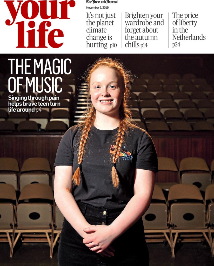 Editorial photo by Scott Cameron Baxter. Photo shows a young woman standing with her arms at front with hands in front of her waist looking straight into the camera, pictured in front of seating looking onto a stage, She is wearing all black with red hair.
