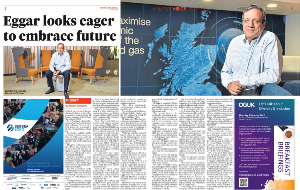 Editorial and PR Photography Aberdeen. A man in the Oil and Gas Authority poses for a photograph in front of a Scottish country map printed onto a wall in blue. The man is wearing dress trousers and a light blue shirt.
