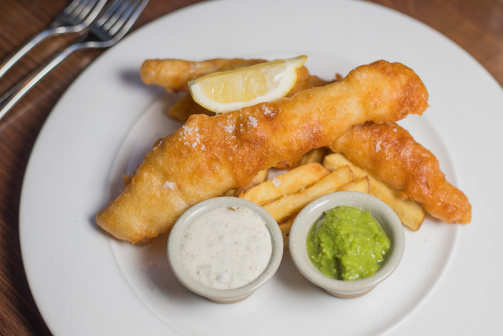 Food Photography Aberdeen by Scott Cameron Baxter. Picture shows battered fish and chips with mushy peas and tartar sauce on a white plate photographed top down.