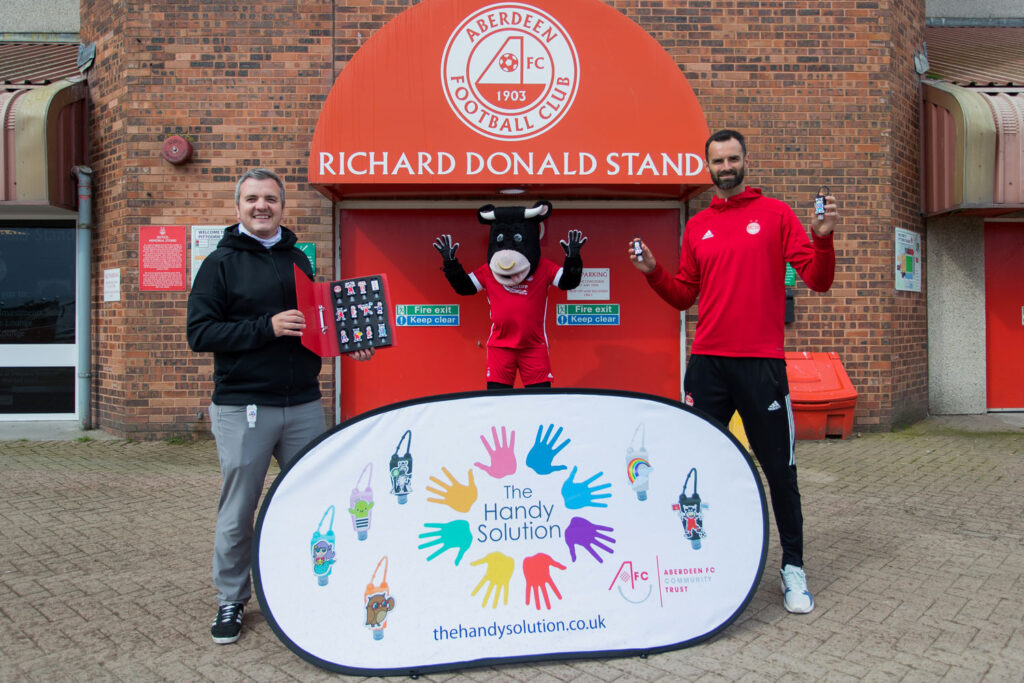 A photograph of two people holding hand sanitiser two meters apart with Aberdeen FC mascot Angus the bull in the background centre infant of a red brick wall at the Richard Donald Stand, Pittodrie Stadium. Picture by Scott Cameron Baxter for a PR photoshoot for Aberdeen FC.