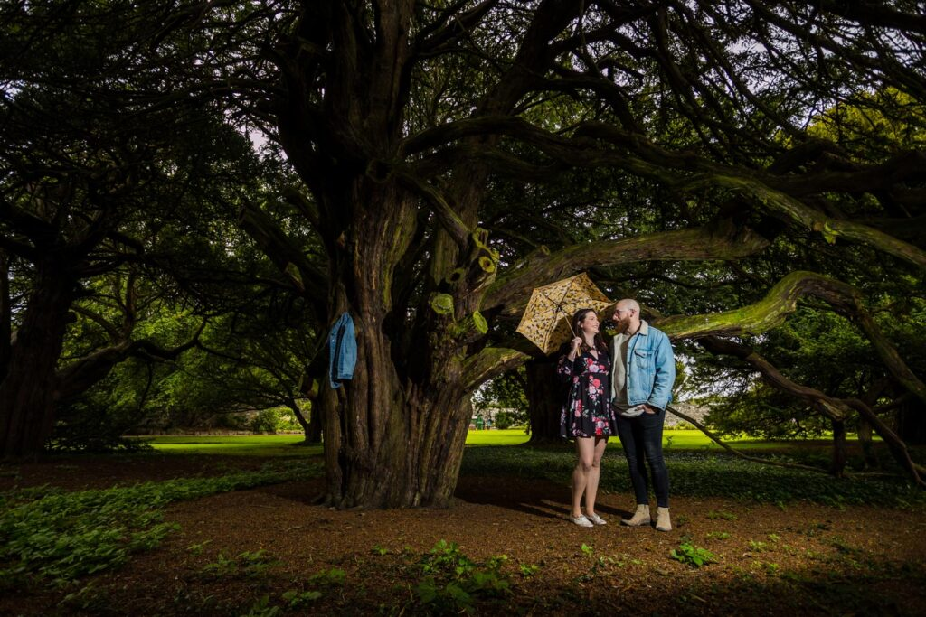 A couple pose in Ellon Castle Gardens for an engagement photoshoot. A sunny day and the couple are photographed under the cover of overhanging trees. The couple are facing one another while holding hands. She wears a dress floral dress while holding a yellow umbrella and he wears a blue wash denim jacket with sheepskin collar with dark jeans.