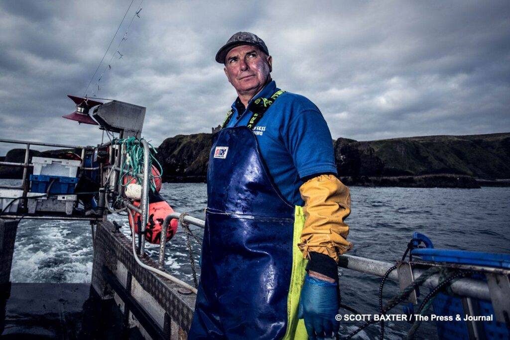 A fisherman at sea wearing a blue coverall with yellow waterproof arm protection look over the camera into the distance while hauling for Lobsters off the coast of Stonehaven, Scotland. Press Release photography by Scott Cameron Baxter, Aberdeen, Scotland.