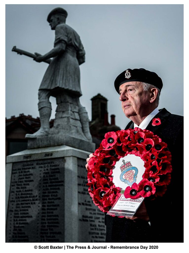 A veteran stands in front of Ellon War memorial statue, In Ellon, Scotland, while holding a red poppy wreath looking away from the camera.