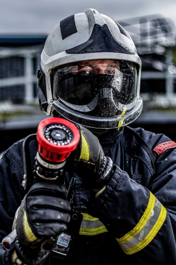 Commercial Photographer Aberdeen - Scott Cameron Baxter. Image shows a man during a offshore survival fire training course holding a hose with a wet helmet and visor.